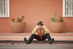 Sad Businessman. Sad Caucasian businessman sits on a curb Stock Image