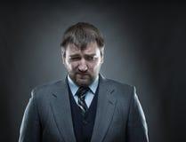 Sad businessman agaist gray. Sad businessman agaist dark gray background Royalty Free Stock Images