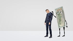 A sad businessman being assured by a large dollar bill with arms and legs that pats the man`s back. Royalty Free Stock Photography