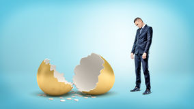 A sad businessman on blue background looks down on a giant broken golden egg. Royalty Free Stock Photography