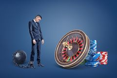 A sad businessman chained to an iron ball stands near a casino roulette and chip stacks. Gambling debt. Debt loan. Business foreclosure stock image