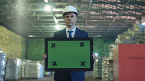 Sad businessman with chromakey sign. Angry or unhappy man in warehouse standing and holding a pad for copy space. Horizontal indoors shot stock video