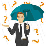 Sad businessman hiding from question marks with umbrella Stock Photo