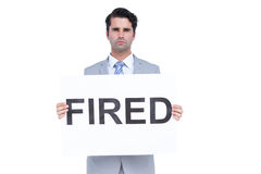 Sad businessman holding a fired sign Royalty Free Stock Photos