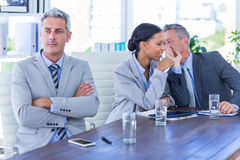 Sad businessman looking aways while his colleagues speaks Stock Photos