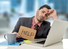 Sad businessman at office desk working on computer laptop asking for help depressed Royalty Free Stock Photo