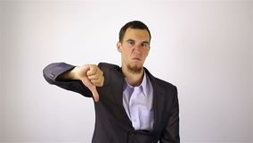 Sad businessman with a beard showing dislajk. Sad businessman showing dislajk gesture. on grey Background stock footage