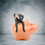 Sad businessman sitting on big piggy bank. And looking down Royalty Free Stock Photo