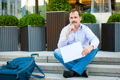 Sad businessman sitting on the steps Royalty Free Stock Image