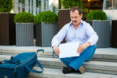 Sad businessman sitting on the steps Stock Images