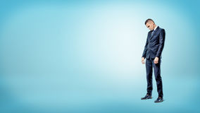 A sad businessman standing on blue background looking down with slumped shoulders. Royalty Free Stock Photos