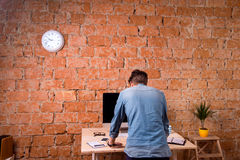 Sad businessman standing at office desk, rear view. Sad businessman standing at office desk, against brick wall. Computer on the table. Smart phone, personal Stock Photos