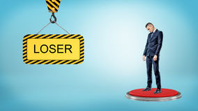 A sad businessman stands on a large red button near to a construction sign with a lettering LOSER. Stock Photo