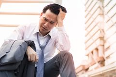 Sad businessman with suit sitting at stair walk way in city after business project fail stock image