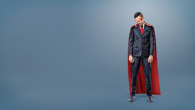 A sad businessman in a superhero red cape standing on dark blue background with his shoulders slumped. Stock Images