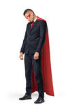 A sad businessman in a superhero red cape standing with his shoulders slumped and looking down. Royalty Free Stock Photography