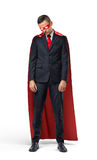 A sad businessman in a superhero red cape standing with his shoulders slumped and looking down. Stock Images