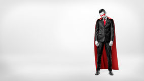 A sad businessman in a superhero red cape standing on white background with his shoulders slumped. Royalty Free Stock Image