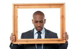 Sad businessman with wooden frame Stock Image