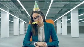 Sad businesswoman blowing a festive whistle, wearing a birthday cap. 4K stock video footage