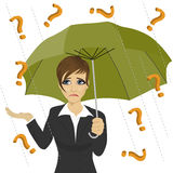 Sad businesswoman hiding from question marks with umbrella Stock Image
