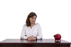 Sad businesswoman looking at piggy bank Royalty Free Stock Photo