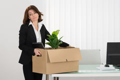 Sad Businesswoman Packing Her Belongings In Box Stock Images
