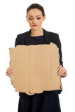 Sad businesswoman with piece of cardboard. Royalty Free Stock Image