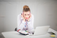 Sad businesswoman sitting at the desk in the office. Portrait of sad and stressed businesswoman at the desk in the office. Life of modern female concept Royalty Free Stock Image