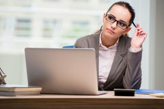 The sad businesswoman working at her desk Stock Images