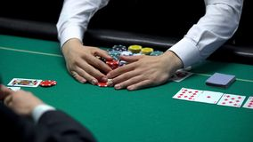 Sad casino player losing poker game, professional croupier taking all chips. Stock photo stock photography