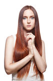 Sad casual female. Vertical studio portrait of young attractive green-eyed caucasian female with long natural straight red hair which holding her hand together royalty free stock photography