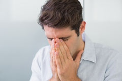 Sad casual young man with hands to his face Royalty Free Stock Photography