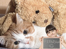 Sad cat. Caucasian little girl hold chalkboard signed friendship with red cat lying with rabbit toy Royalty Free Stock Photo