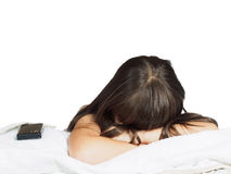 Sad caucasian child kid girl sister lying on the bed with mobile phone isolated Royalty Free Stock Photo