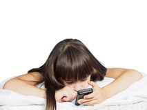 Sad caucasian child kid girl sister lying on the bed with mobile phone isolated Royalty Free Stock Photography