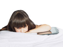Sad caucasian child kid girl sister lying on the bed with mobile phone and tablet pc isolated Royalty Free Stock Photo
