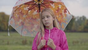 Sad caucasian girl with blonde hair and light brown eyes dressed in pink jacket holding collorful umbrella with painted. Yellow leaves. Pretty girl spending stock video
