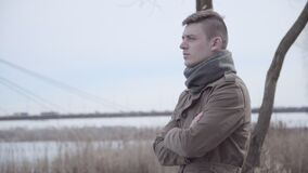 Sad Caucasian man standing on riverbank and thinking. Portrait of young depressed lonely guy spending spring or autumn