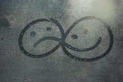 Sad and cheerful smiles on wet glass. Sad and cheerful smiles on rainy glass Stock Image