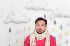 Sad cheerless man looking sadly in front of him. Feeling unwell. Moody upset bearded man wearing a knitted scarf and looking in front of him while standing Royalty Free Stock Photos