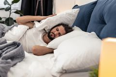 Sad cheerless man not wanting to get up. Its so difficult. Sad cheerless man holding pillows while not wanting to get up royalty free stock photography
