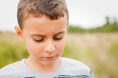Sad child. Looking down, outdoors with a forest in background, shallow depth of field Royalty Free Stock Photo