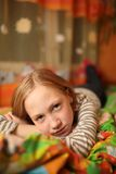 Sad child. Girl lying on bed, looking at camera Royalty Free Stock Photo