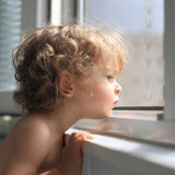 Sad child. Looking out of the window stock images
