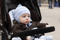 Sad child. The sad child is sitting in stroller royalty free stock photography