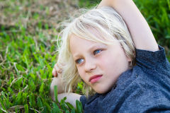 Sad child alone in park. Sad, worried child alone lying on grass in park royalty free stock image