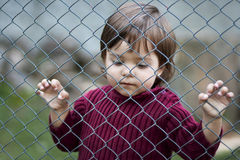 Sad child behind fence. Sad and lonely kid grabbing a wire fence feeling locked away and captive Stock Photography