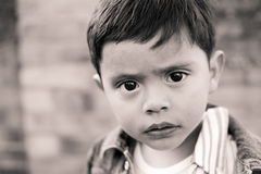 Sad child with big eyes. Small child with a sad look, with big, dark beautiful eyes looking right into you.   Beautiful little boy with stunning eyes.  It looks Stock Images