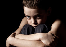 Sad child on black. Sad boy on black background. Portrait depression boy Stock Photos